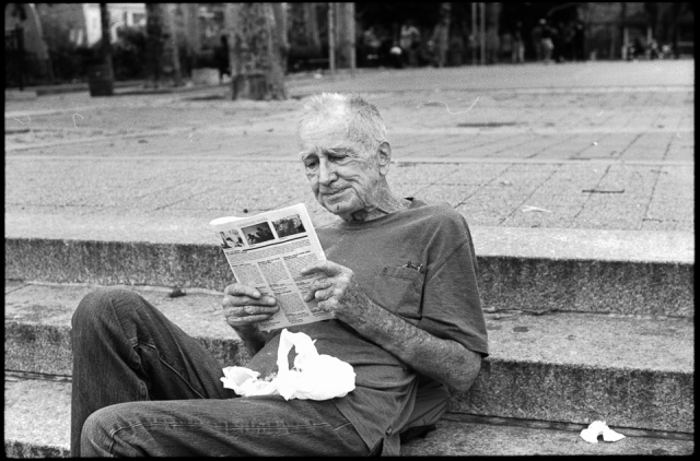 25 Oct. 2015 - New York City - A man reads the news while sitting on the steps just outside of Sara D. Roosevelt Park on a pleasant fall afternoon.