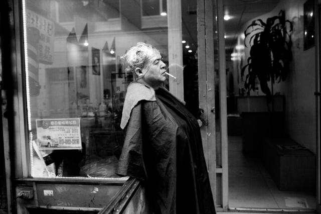 A man takes a smoke break outside of a hair salon - Bowery. ©Sarah Blesener