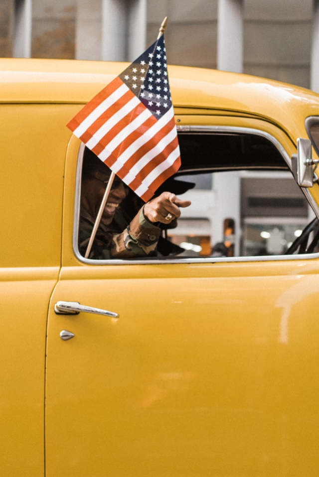 Army veteran participating in America's Parade from the passenger seat of an American classic car on November 11, 2015. ©Leda Costa