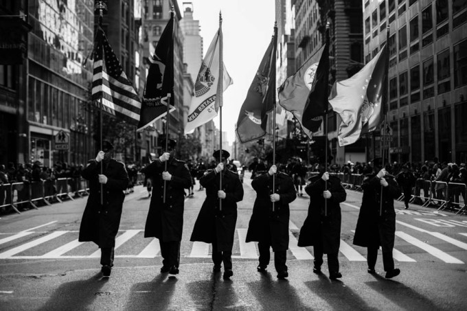 Members of Port Authority Police Department Marine Corps Association hold up flags.